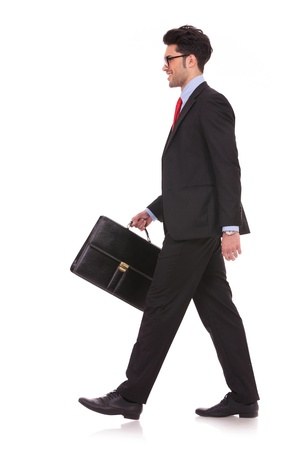 side view full length picture of a young business man walking forward with a briefcase in one of his hands and looking away from the camera on white background photo