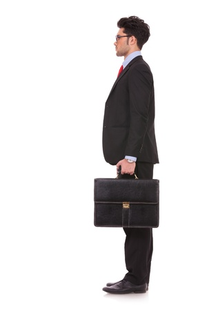 side view full length picture of a young business man standing with his suitcase in his hand and looking straight forward, away from the camera on white background photo
