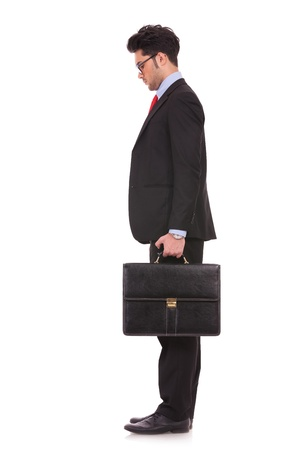 man looking down: side view full length picture of a young business man standing with his suitcase in his hand and looking down, in front of him on white background Stock Photo