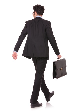 back view full length picture of a young business man walking with his suitcase and looking at something in a side direction on white background photo