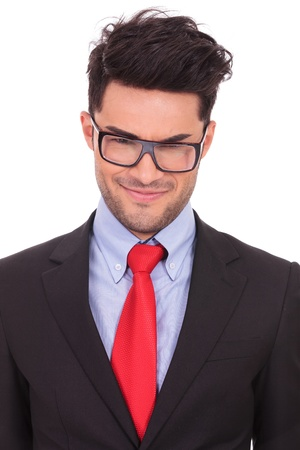 frowned: closeup portrait of a young business man looking at the camera with a malitious look on his face, on a white background  Stock Photo
