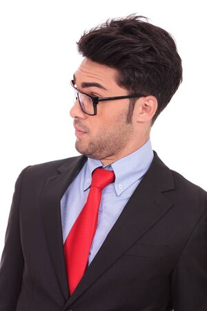 raised eyebrows: portrait of a young business man looking amazed at something from his side, on white background