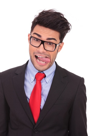 closeup portrait of a young business man making a fool out of himself, sticking his tongue out, on a white background photo