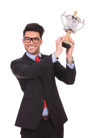 business man raising his trophy and smiling to the camera, on white background photo