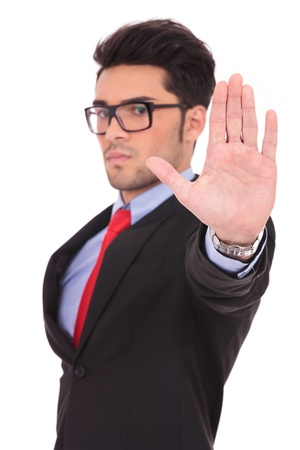 talk to the hand: portrait of a young business man showing the stop sign with his palm and looking at the camera, on white Stock Photo