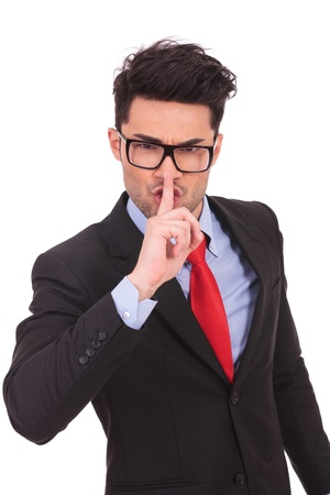 young business man showing the shut up sign with his finger against his mouth on a white wallpaper