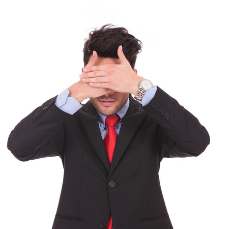 hide and seek: young business man covering his eyes with both his hands, on white background