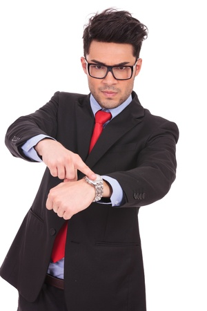 demanding: young business man pointing angrily to his watch and looking at the camera, on a white background Stock Photo