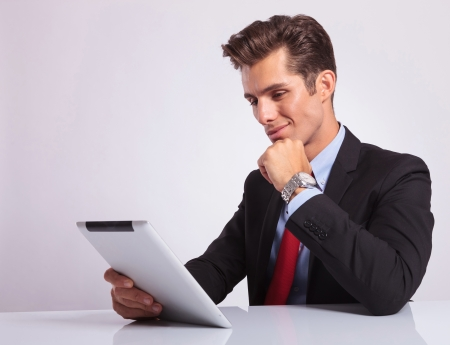 young business man sitting at desk and reading pensively on his tablet, on gray background photo