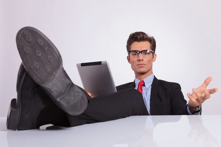 young business man sitting with his legs on the desk and holding a tablet is looking at the camera and questioning you, on gray background photo