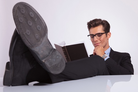 young business man sitting with his feet on the desk and reading a book thoughtfully, on gray background photo