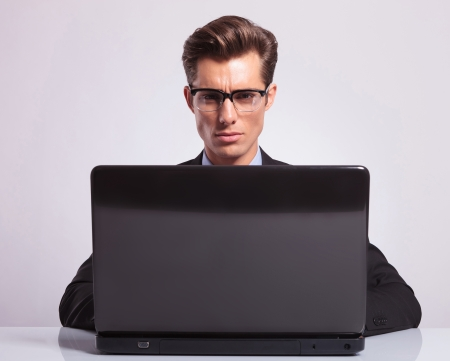 close-up picture of a young attractive business man working at his laptop and looking into the camera, on a gray background photo