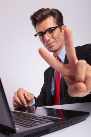 victory stand: closeup of a young business man sitting at the laptop and showing victory sign, focus on his face, on grey background Stock Photo