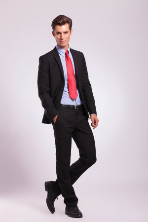 full suit: full length picture of a young business man standing with a hand in his pocket, legs crossed, and looking into the camera, on a gray background