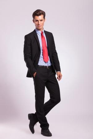 traje: imagen de cuerpo entero de un joven hombre de negocios de pie con una mano en el bolsillo, con las piernas cruzadas, y mirando a la c�mara, sobre un fondo gris