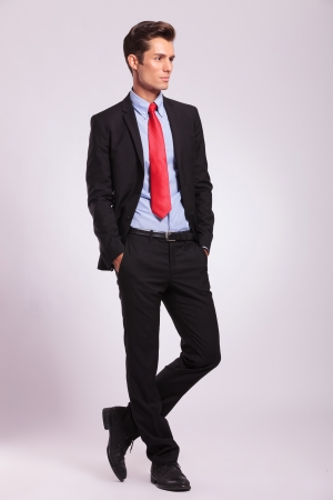 young business man standing with hands in his pockets and looking away from the camera, on gray photo