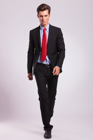bussiness: business man walking towards the camera and looking forward with a serious look, on gray  Stock Photo