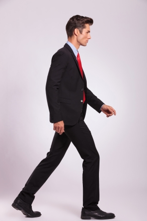 view of an elegant office: side portrait of a young business man walking on gray background and looking away