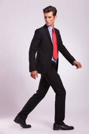 full length picture of a young business man walking forward and looking back - side view  photo