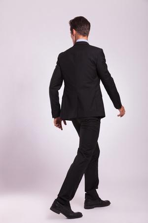 achteraanzicht van een jonge zaken man lopen en op zoek naar zijn kant, op een grijze achtergrond
