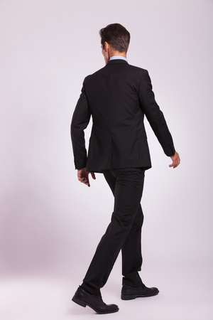 suit case: back view of a young business man walking and looking to his side, on gray background
