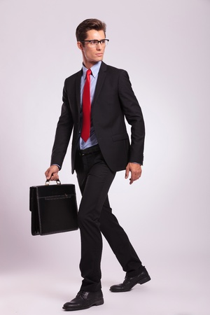 business man walking with a briefcase and looking away, on gray photo
