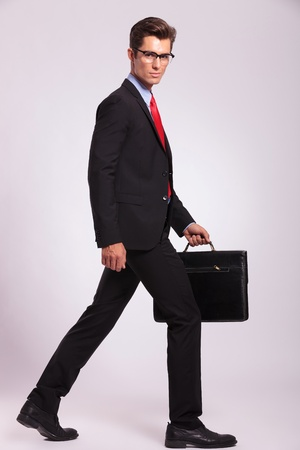 brief case: young business man is walking and looking at the camera while holding a suitcase . gray background Stock Photo