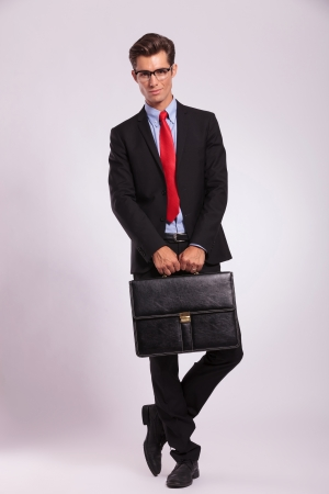 certitude: smiling young business man is standing with legs crossed and holding a suitcase with both hands, against gray background