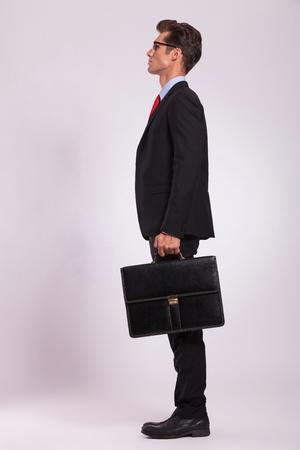při pohledu na fotoaparát: boční pohled na vážný mladý muž stojí s kufrem v ruce a díval se dál od kamery, na šedé