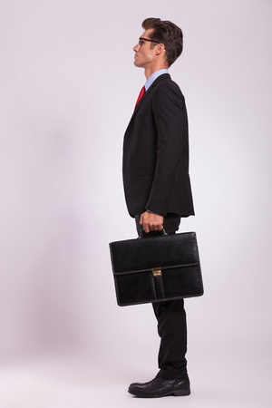 looking to the side: side view of a serious young man standing with a suitcase in his hand and looking away from the camera, on gray Stock Photo