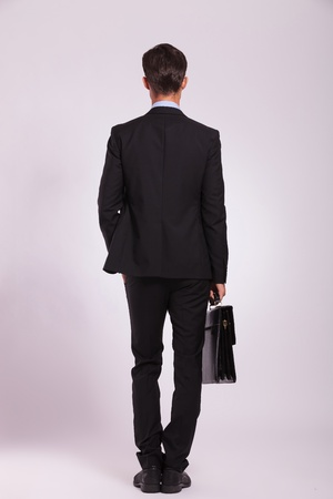 back view of a young business man standing with a hand in the pocket and holding his briefcase with the other, on gray photo