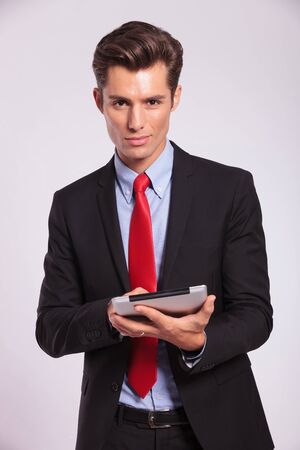 young business man holding a touch screen pad and looking to the camera, smiling on gray photo
