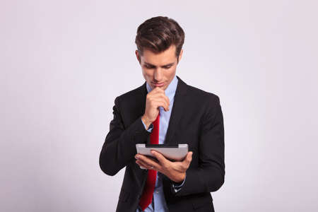 touch pad: young business man holding a tablet and contemplating while looking at it. on gray Stock Photo