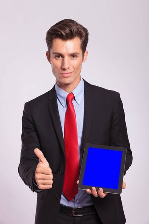 young business man presentig tablet and showing thumb up, on gray background photo