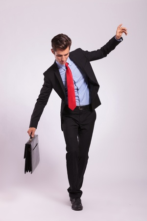 precipitate: Business man holding a briefcase balancing and walking forward on an imaginary rope on gray background