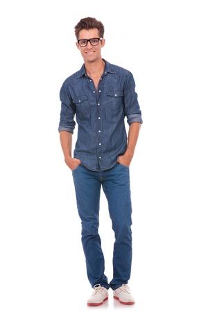 poses de modelos: vista frontal de un hombre joven casual de pie con las manos en los bolsillos y sonriendo a la cámara. aislado en un fondo blanco