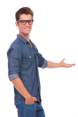 indicating: cutout picture of a casual young man standing with a hand in his pocket and presenting something in the back while smiling to the camera. isolated on a white background