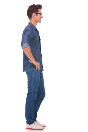 see side: side view of a casual young man standing with his hands on his hips and looking away from the camera. isolated on a white background
