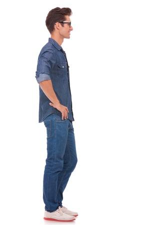 side pose: vista lateral de un hombre joven casual de pie con las manos en las caderas y mirando fuera de la c�mara. aislado en un fondo blanco