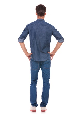 hands on hip: back view of a casual young man standing with his hands on his hips. isolated on a white background