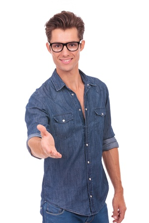 cool guy: waist-up picture of a casual young man welcoming you with a handshake and a warm smile on his face. isolated on a white background Stock Photo