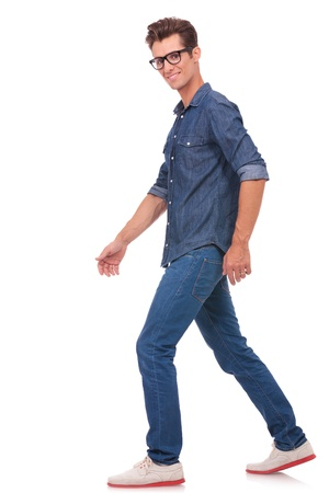 looking away from camera: casual young man walking away from the camera while looking at it. isolated on a white background
