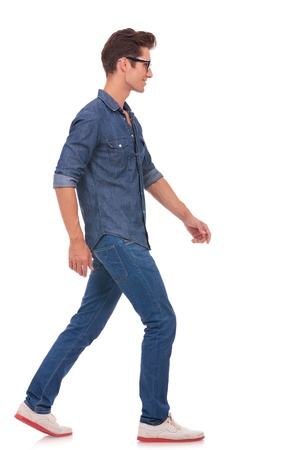 side pose: side view of a casual young man walking and looking forward, away from the camera. isolated on a white background