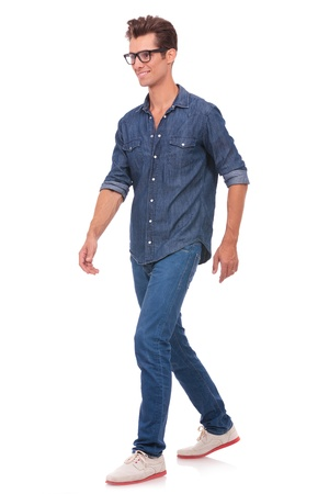 full length: casual young man walking and looking forward, away from the camera, with a smile on his face. isolated on a white background