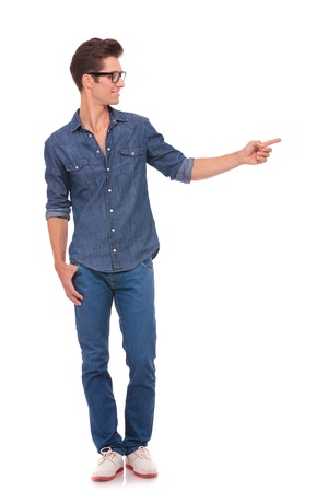 standing man: casual young man standing with a thumb in his pocket and pointing and looking to his side with a smile on his face. isolated on a white background
