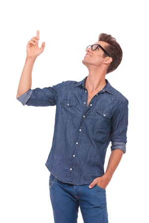 cool boys: casual young man pointing and looking upwards while holding a hand in his pocket and smiling. isolated on a white background
