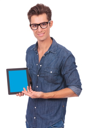 portrait of a casual young man presenting his tablet and smiling to the camera. on white background photo