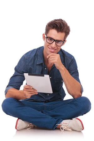 casual young man sitting on the floor with his legs crossed and holding a tablet and rubbing his chin while smiling to the camera. isolated on white photo