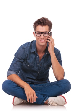 casual young man sitting cross legged and talking on the phone while smiling to the camera. isolated on white photo