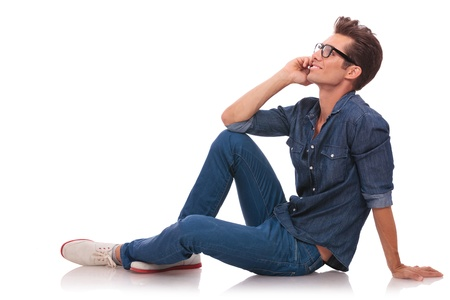 see side: side view of a casual young man sitting on the floor and speaking on th phone while looking away from the camera. isolated on white